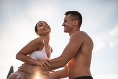 Pleased lady laughing and young man touching her waist stock photos