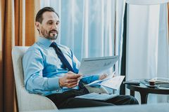 Waist up of businessman working with charts in hotel room stock images