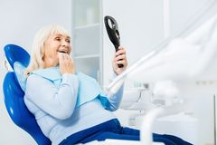 Waist up of delighted woman in dental office. Cheerful smile. Waist up of delighted women sitting on dental chair while looking in the dental mirror and being royalty free stock photo