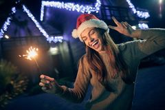 Waist up of a joyful smiling woman holding a sparkler outdoors. Waist up of a joyful young beautiful woman enjoying her winter holidays while holding a spartling stock photo