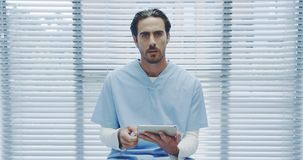 Young male doctor using tablet and talking to camera 4k stock video footage