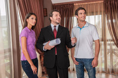 Waist up of male real estate agent smiling with two clients. Happy agent holding plan of new apartment and looking away Stock Photos