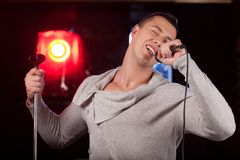 Waist up of male singer holding stand. Handsome man singing into microphone alone Royalty Free Stock Image
