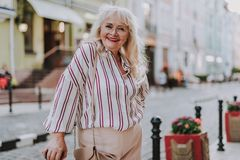 Old smiling woman standing on the street stock image