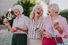 Three stylish old women make fun together royalty free stock photo