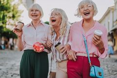 Three smiling ladies walking in the city stock images