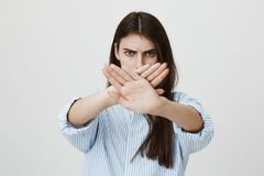 Waist-up portrait of anxious and serious brunette crossing hands in stop or enough gesture, looking angry at camera. While standing over gray background. Girl royalty free stock photo