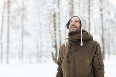 Smiling Adult Man Enjoying Winter. Waist up portrait of bearded man in winter forest having fun and enjoying snow, copy space royalty free stock photos