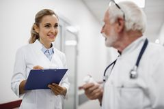 Smiling nurse looking at doctor while standing in hospital hallway stock photography