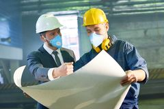 Expansion Discussion at Plant. Waist up portrait of businessman and worker discussing floor plans at plant, holding large blueprint, both wearing protective Royalty Free Stock Photo