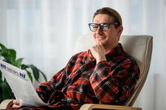 Satisfied adult male reading the journal in room. Waist up portrait of calm man looking at camera with glad smile. He is sitting in chair indoors and holding the royalty free stock photo