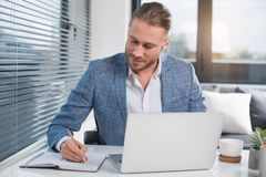 Tranquil executive doing his job. Waist up portrait of calm manager working in the office. He is sitting at the table and writing in the pad Stock Image