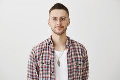 Waist-up portrait of calm and successful young businessman, wearing glasses and smiling at camera. Young entrepreneur. Listens to customers complaints. Office Royalty Free Stock Images