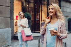 Beautiful middle-aged lady holding shopping bags while standing on the street royalty free stock images