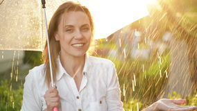 Waist Up Portrait Of Cheerful Girl Holding Umbrella And Catching Rain Drops With Smile. She is Stretching Hand And stock footage