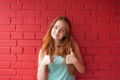Girl with sweet appearance. Waist-up portrait of cheerful young model showing thumbs up on red brick wall. Smiling happy lady in stylish clothes. Advertisement stock photo