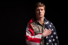 Upset male soldier believing in his country. Waist up portrait of cheerless military young man looking at camera and putting his hand on heart with sad look Stock Photos