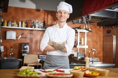 Handsome Chef Posing. Waist up portrait of handsome chef posing in kitchen standing with arms crossed, copy space stock photography