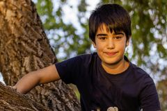 Waist-up portrait of handsome happy smiling young boy in park. royalty free stock image
