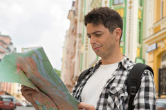 Waist-up portrait of handsome male traveler on the. Waist-up portrait of dissatisfied handsome male traveler on the street holding a map in his hands and looking Stock Photos