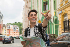 Waist-up portrait of handsome male traveler on the. Waist-up portrait of happy handsome male traveler on the street holding a map in his hands and showing ahead Stock Photo
