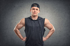 Waist-up portrait of handsome muscled young man with his hands on hips. Stock Photography