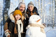 Family Posing with Snowman royalty free stock photo