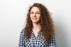 Waist up portrait of happy female with cheerful expression, curly hair, dressed in checkered shirt, isolated over white background Stock Photo