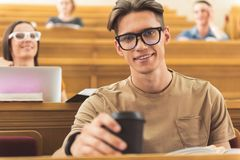 Joyful young man enjoying hot beverage at lecture hall. Waist up portrait of happy guy drinking coffee and smiling. He is sitting at table in auditory room at stock photos