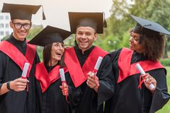 Excited graduates presenting their certificates of higher education Royalty Free Stock Images