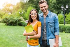 Cheerful man and woman resting in nature after studying. Waist up portrait of happy young students standing and embracing in park. Girl is keeping folder with Royalty Free Stock Image