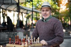 Happy mature male pensioner relaxing near chessboard in park royalty free stock photo