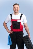 Waist up portrait of mechanic holding spare tire. Royalty Free Stock Photo