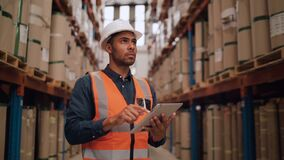 Waist up portrait of modern African American warehouse worker using digital tablet looking up at tall shelves in the