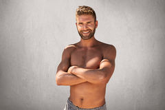 Waist up portrait of muscular attractive man with trendy hairstyle and bristle, keeping his hands crossed  ovre grey backg. Round. Strong handsome male smiling Royalty Free Stock Photo