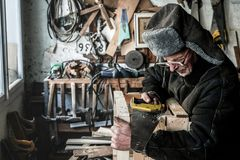 Waist up portrait of old grandfather in grey warm clothes in eyeglasses sawing wooden plank royalty free stock images
