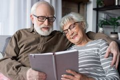 Charming senior couple relaxing on sofa with book stock images
