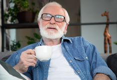 Thoughtful mature man enjoying jot coffee. Waist up portrait of pensive pensioner resting on sofa at home. He is holding cup of hot drink and wisely smiling Stock Images