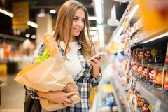 Pretty Young Woman in Supermarket. Waist up portrait of pretty young woman using smartphone and holding bag with groceries while  choosing food in supermarket Royalty Free Stock Images