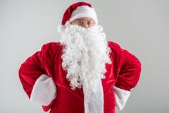 Cheerful Father Frost posing in red and white costume. Waist up portrait of proud bearded Santa Claus standing with arms akimbo. He is looking at camera and Stock Photography