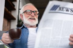 Smart old reader enjoying morning news. Waist up portrait of retired man laughing while reading publication. Focus on paper while pensioner is holding cup of Royalty Free Stock Image