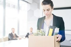 Sad Businesswoman Leaving Job. Waist up portrait of sad businesswoman holding box of personal belongings leaving office after being fired job, copy space royalty free stock photo