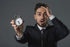 Young businessman is shocked about time. Waist up portrait of scared and discouraged man clutching head and showing time at snooze. Focus on alarm clock Stock Image