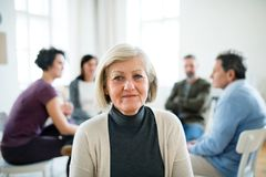 A portrait of senior depressed woman during group therapy. royalty free stock photography