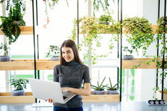 Waist up portrait of serious young businesswoman holding laptop computer while concept modern office Stock Images