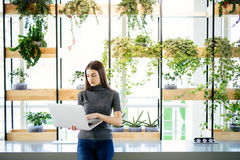 Waist up portrait of serious young businesswoman holding laptop computer while concept modern office Stock Image