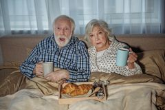 Horrified pensioners watching TV at home. Waist up portrait of shocked elderly men and women sitting in bed. They are holding cups and having meal while looking Royalty Free Stock Images