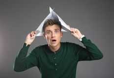 Amused guy holding records above his head. Waist up portrait of shocked male person relaxing on chair and taking cover under papers. on background stock image