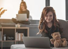 Little curly girl smiling with laptop at home. Waist up portrait of small, red-haired kid using her computer and looking at camera with happiness. Her mother is Stock Photography
