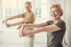 Glad mature couple stretching their hands. Waist up portrait of smiling aging women standing with outstretched arms. Man in same posture on background. Focus on Royalty Free Stock Photos